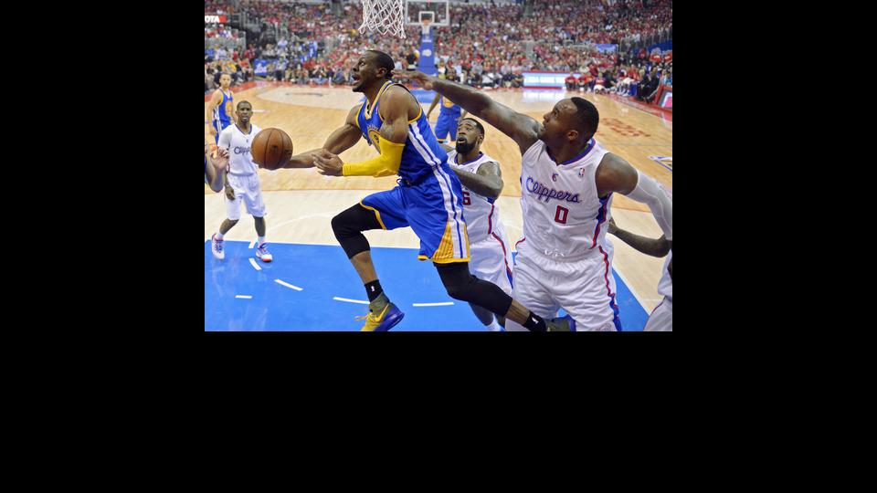 Golden State Warriors forward Andre Iguodala, left, puts up a shot as Los Angeles Clippers center DeAndre Jordan, center, and forward Glen Davis defend during the first half in Game 1 of an opening-round NBA basketball playoff series, Saturday, April 19,