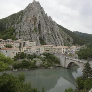 The pack passes a bridge spanning Durance river in Sisteron during the fifteenth stage.