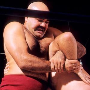 Kubla Khan (red) applies a double wristlock against Mike DeBiasie at Hollywood Legion Stadium in Los Angeles