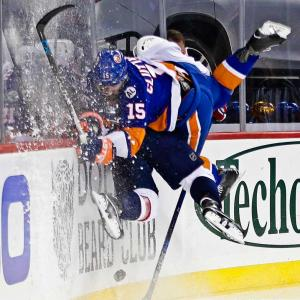Here are some of the images that caught our eye on the sports night of Feb. 18, beginning with Cal Clutterbuck (15) checking Dmitry Orlov during the Islanders-Capitals game.