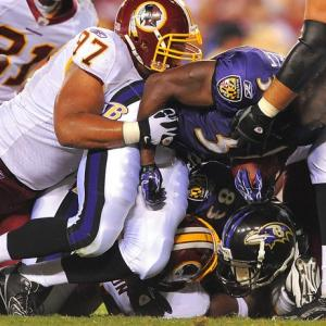 Baltimore Ravens running back Jalen Parmele loses his helmet but holds on to the ball as he's stopped by Washington Redskins defenders at FedEx Field in Landover, Maryland. The Ravens won 23-3.