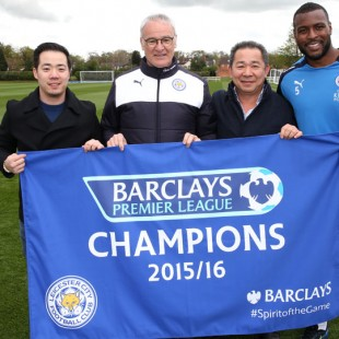 Claudio Ranieri holds up Leicester's banner for winning the Premier League