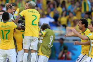 Brazil goalkeeper Julio Cesar is mobbed by his teammates after making two saves in a penalty shootout triumph over Chile in the World Cup round of 16.