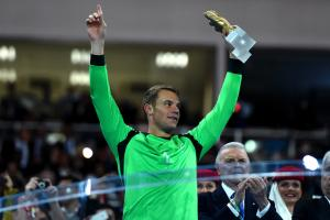 Germany's Manuel Neuer hoists his individual hardware after claiming the Golden Glove as the World Cup's best goalkeeper.