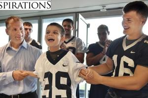 Dante Chiapetta, with help from his father, Joe and Yale sophomore tight end Jackson Stallings, shows off his new jersey after signing paperwork to join the Yale Bulldogs football team as part of the Team Impact charity.