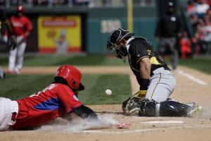 Pittsburgh Pirates catcher Tony Sanchez, right, tries to handle the throw from the outfield as Philadelphia Phillies' Odubel Herrera scores on a single by Carlos Ruiz during the second inning of an exhibition baseball game, Saturday, April 4, 2015, in Phi