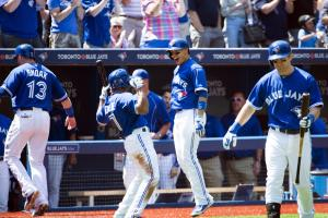 Toronto Blue Jays' Ryan Goins, second from right, celebrates with teammate Ben Revere after hitting a three-run home run against the Oakland Athletics during the second inning of a baseball game in Toronto, Thursday, Aug. 13, 2015. (Darren Calabrese/The C