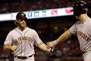 San Francisco Giants' Madison Bumgarner, left, is congratulated by teammate Buster Posey after scoring during the seventh inning of a baseball game against the St. Louis Cardinals, Tuesday, Aug. 18, 2015, in St. Louis. (AP Photo/Jeff Roberson)