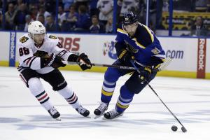 Chicago Blackhawks' Patrick Kane, left, reaches for St. Louis Blues' Patrik Berglund, of Sweden, during the first overtime in Game 5 of an NHL hockey first-round Stanley Cup playoff series Thursday, April 21, 2016, in St. Louis. (AP Photo/Jeff Roberson)