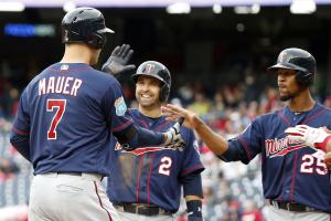 Minnesota Twins' Joe Mauer (7) celebrates knocking in Brian Dozier (2) and Byron Buxton (25) with a three-run home run during the third inning of an exhibition baseball game against the Washington Nationals at Nationals Park, Saturday, April 2, 2016, in W