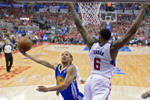 Golden State Warriors guard Stephen Curry, left, puts up a shot as Los Angeles Clippers center DeAndre Jordan defends during the first half in Game 1 of an opening-round NBA basketball playoff series, Saturday, April 19, 2014, in Los Angeles. (AP Photo/Ma