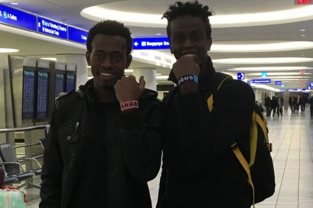 Somalian refugees Saad Hussein and Saddiq Mohammed show off bracelets with their names as they are reunited at an airport in St. Louis