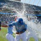 Alcides Escobar is doused by teammates Salvador Perez and Kelvin Herrera following the Royals 4-1 win over the Indians. Escobar went 3-for-3 in the game, extending his hitting streak to 10 games.