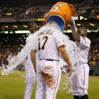 Gaby Sanchez is doused by teammates Andrew McCutchen and Josh Harrison after his game-winning sacrifice fly in the Pirates 3-2 win over the Braves.
