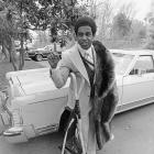 Dallas Cowboys star running back Tony Dorsett standing beside his car, holding up a number one sign, and resting against his crutches. Dorsett was a four time Pro Bowl pick.