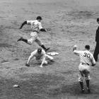Joe DiMaggio leaps for first base as Johnny McCarthy vainly tries to stop Mel Ott's wild throw in the 3rd inning of Game 4 of the World Series on Oct. 9, 1937 at the Polo Grounds in New York.