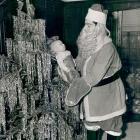 Joe DiMaggio plays Santa Claus with his newborn son, Joe DiMaggio III, in Dec. 1941.