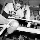 Ted Williams weighs one of his new 36-ounce Hickory baseball bats in the clubhouse after morning workout at spring training in 1948.