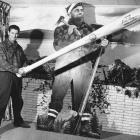 Proclaimed a modern-day Paul Bunyan, Ted Williams poses with an eight-foot bat in front of a picture of the legendary logger in 1958.