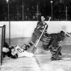 """Toronto goalie Johnny Bower barely avoided being bowled over by Bernie """"Boom Boom"""" Geoffrion during the first period in Game 4, but there was no stopping Montreal's steamrolling Habs. Making their 10th straight appearance in the final, the Canadiens captured their record fifth consecutive Cup by sweeping the Leafs. The series finale marked the final NHL game of the great Rocket Richard."""