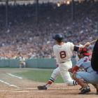 Carl Yastrzemski hits a home run as St. Louis Cardinals catcher Tim McCarver looks on during Game 2 of the World Series at Fenway Park in Boston on Oct. 5, 1967.