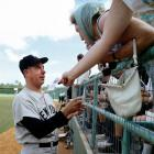 Joe DiMaggio signs autographs for fans during spring training at Fort Lauderdale Stadium in March 1967.