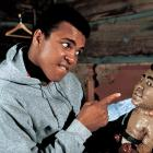 His smaller incarnation stares straight back as Ali plays with a doll of himself during the same 1974 shoot at his training camp cabin.