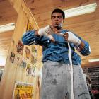 Less than three weeks before his rematch with Joe Frazier on Jan. 28, 1974, Ali wraps his hands while wearing a sauna suit at his training camp cabin.