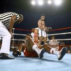 Foreman lies down on the canvas as Ali stands in the background during the Rumble in the Jungle. Ali knocked Foreman down with a five-punch combination in the eighth round, and referee Zack Clayton counted him out.
