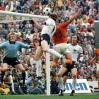 Berti Vogt of West Germany heads the ball as Dutchman Johan Cruyff and teammate Franz Beckenbauer look on in the 1974 World Cup.