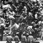 Spanish riot police look on as English and French fans topple barriers as a result of fighting in the stands during England's 3-1 win over France in the 1982 World Cup.