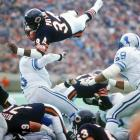 """Payton lunges over defenders to score against the Detroit Lions on Nov. 18, 1984. """"Sweetness"""" was no stranger to the end zone, scoring 125 touchdowns in his career."""