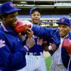 Mike Tyson throws a mock punch at New York Mets pitcher Dwight 'Doc' Gooden as Darryl Strawberry looks on.