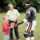 """Even singer Phil Collins wanted some """"Sweetness"""" memorabilia. Collins, with his son Simon, receives an autograph from Payton before the 1986 Bears-Cowboys regular season contest dubbed the """"American Bowl."""""""