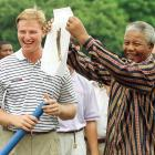 Ernie Els and Mandela laugh before the final round of the Alfred Dunhill South African PGA Championship as Mandela shows the crowd a sketch of Els.