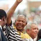 Mandela salutes the crowd before a football match in Johannesburg, where South Africa defeated Cameroon 3-0.