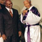 World heavyweight boxing champion Evander Holyfield looks on as Mandela wears Holyfield's gift, a boxing gown. Holyfield stayed in South Africa for five days to conduct workshops and advocate for the importance of education for youth.