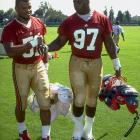 Bryant Young (97) greets teammate Ken Norton Jr. during 49ers training camp.
