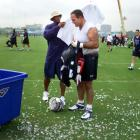 Eddie George gives Bruce Matthews a towel after he was doused with a bucket for his 40th birthday after practice at the Titans' training camp in Nashville, Tenn.