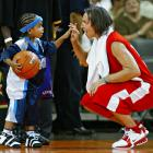 A fan-favorite, Nash squats to high-five one of his young admirers during a charity basketball event.