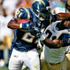 Chargers back LaDainian Tomlinson stiff arms Rams saftey O.J. Atogwe as he takes off on a 38-yard touchdown run.