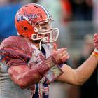 """Tim Tebow displays his """"Christian Warrior"""" image during a muddy game against Florida State in Tallahassee, Fla. The Gators would win 45-15."""