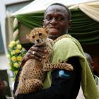 """Bolt holds a cheetah cub at the headquarters of the Kenyan Wildlife Service in Nairobi. Bolt adopted a cheetah and named her """"Lightning Bolt"""" during the Zeitz Foundation launch in Kenya."""