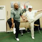 "Charles Barkley stretches with golf instructor Suckki Jang during filming for ""The Haney Project."" Barkley, who has a notorious hitch in his golf swing, appeared with the famed swing coach Hank Haney on his show to try to fix Barkley's swing."