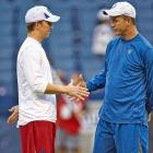 Eli and Peyton Manning shake hands before a Colts-Giants game in Indianapolis.