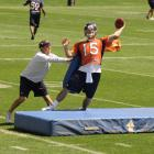 Broncos quarterbacks coach Ben McDaniels pushes Tim Tebow during a passing drill.