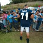 Chargers defensive end Antonio Garay, a man of many hairstyles, signs autographs for fans.