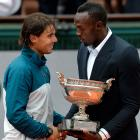 Bolt hands the Musketeers Trophy to French Open winner Rafael Nadal. With the win, the Spaniard became the first player to capture eight Grand Slam titles at the same event.