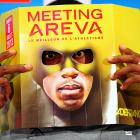 Bolt looks through a leaflet displayed as a mask as he poses after a press conference in Paris.