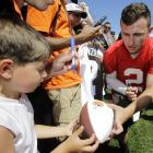 Johnny Manziel hands a football back to a young fan after signing it following practice at the Cleveland Browns' training camp on July 30, 2015 in Berea, Ohio.
